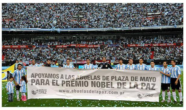 "The banner in this photograph states that the members of the Argentine national football team support the call for the Mothers of Plaza de Mayo to be awarded the Nobel Peace Prize. These are mothers of the 30,000 young men and women who ""disappeared"" under the 1976-83 Argentine military junta. They were killed simply because they were socialists, communists, trade unionists, community organisers, students, activists and so on who opposed the military dictatorship. The mothers have been demanding to know what had happened to their children. The photo has been censured and blocked by mainstream media."