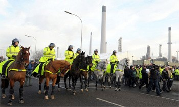 Mounted police stand by as workers protest outside the Lindsey oil refinery in North Lincolnshire