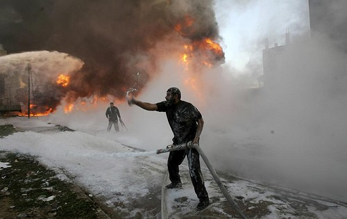 Palestinian firefighters try to extinguish flames at a medical warehouse after an Israeli airstrike (Photo by Amir Farshad Ebrahimi on flickr)