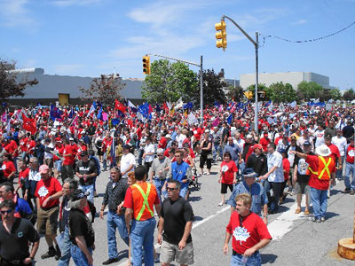 "In June of 2008 General Motors announced the closure of their Oshawa truck plant. A militant demonstration of 5,000 workers marched around the plant with the main slogan ""SAVE OUR JOBS!"""