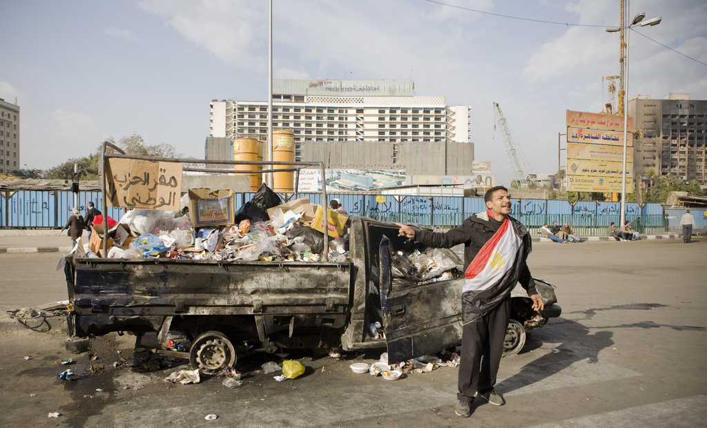 "February 1 - A burnt down police van, turned into a garbage dumb, with a banner: ""NDP Headquarters"" - Photo: 3arabwy"