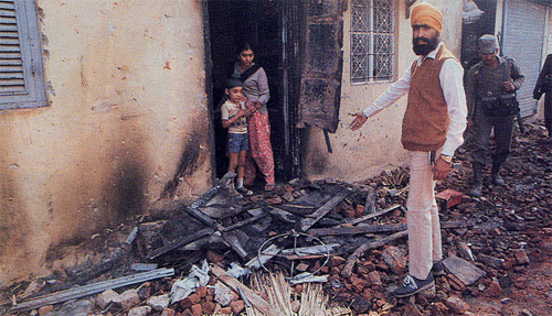 A Sikh family in front of their dwelling after a rampaging mob attacked the property.