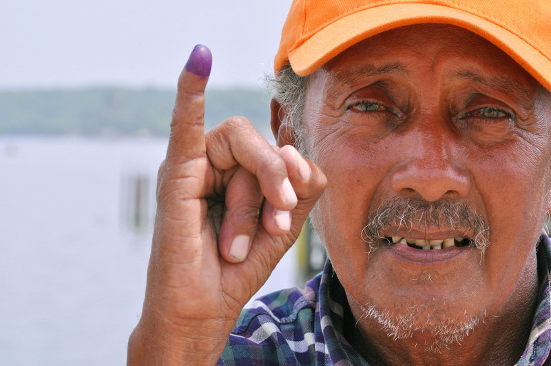 Man showing the blue ink marking someone that has voted. Photo: Héctor Francisco Silva