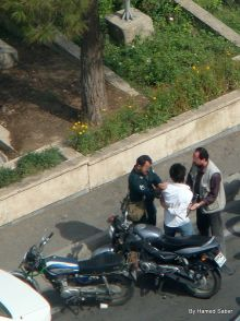 A policeman and a Basiji are arresting a young boy in front of parliament on June 24. Photo by Hamed Saber.