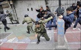 Demonstrators attacking Basij at a demonstration during Ashura