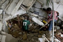 Two Haitians use shovels and their hands to clear rubble in an attempt to reach survivors