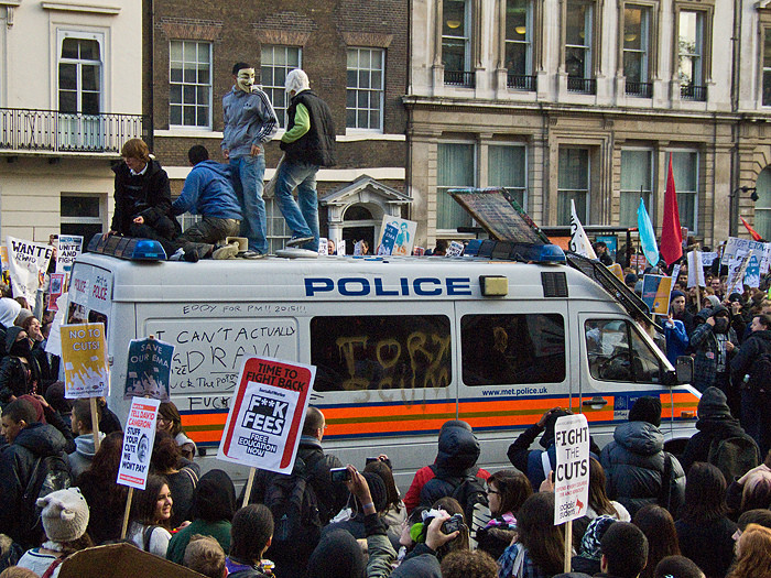 A police van left in the path of the demonstration gets attacked. Photo: Chris Beckett