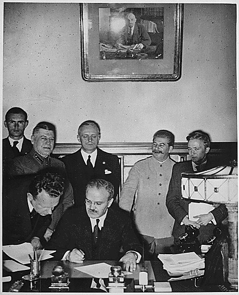 Soviet Foreign Minister Molotov signs the pact. German foreign minister Joachim von Ribbentrop and Josef Stalin stand behind him.