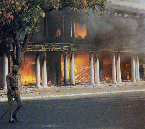 After the outbreak of rioting, a policeman walks past burning shops in downtown New Delhi.